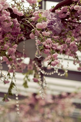 Crystal strands hanging from purple and pink flower vines
