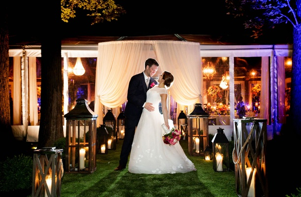 Bride and groom wedding portrait in front of tent reception area lanterns and drapery