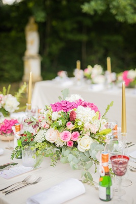 outdoor wedding reception pink and white flowers gold taper candles champagne bottles red goblets