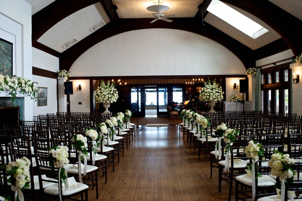 Wedding ceremony in country club ivory rose, greenery bouquets along aisle, mantle, urns