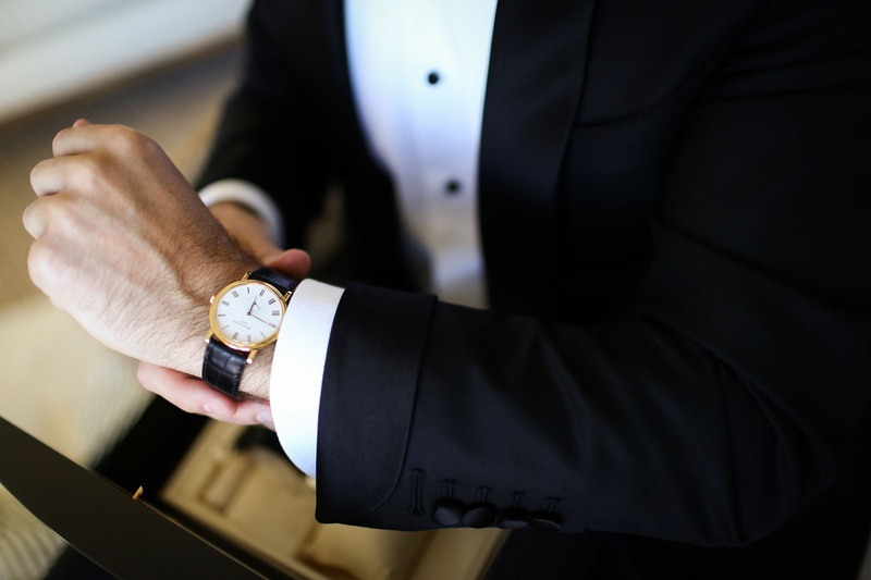groom in tuxedo black buttons black and gold designer watch
