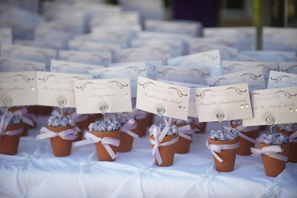 Seating cards with individual flower pots with purple rosettes