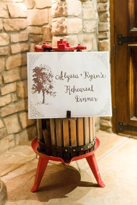Rehearsal dinner sign on wine cask and red stand