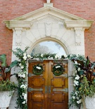 wedding ceremony traditional church service wood doors wreath greenery garlands white flowers decor