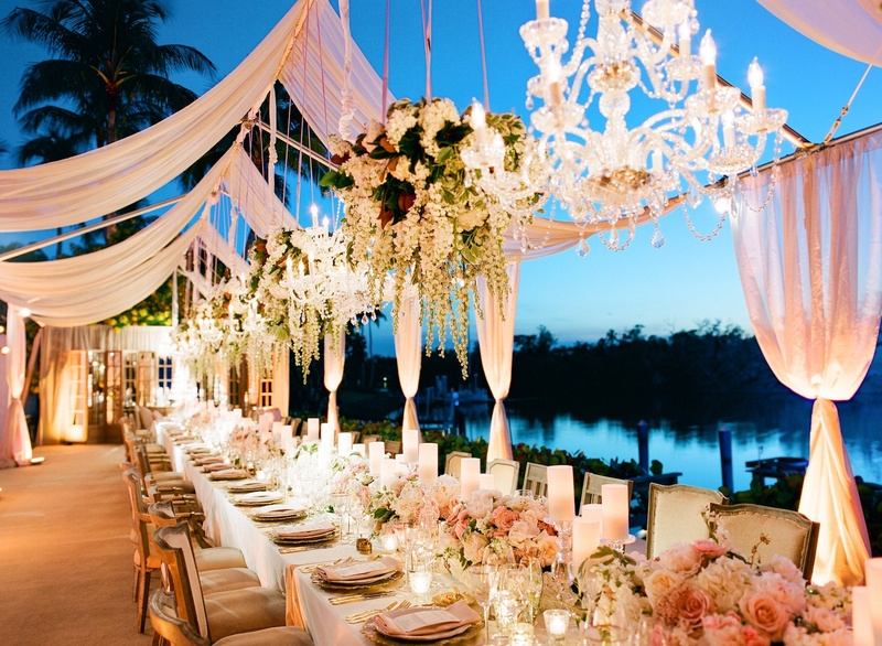 Waterfront wedding reception with sheer pink panels, chandeliers, and floral arrangements