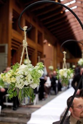 Shepherd hook holding white flowers hanging from rope