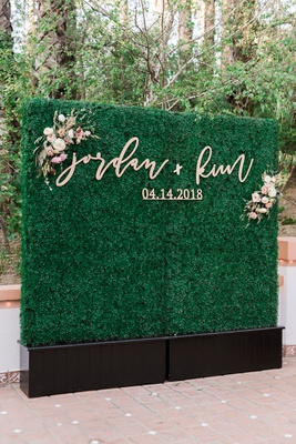 wedding reception green hedge wall gold calligraphy sign couple names date flowers photobooth