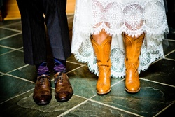 Bride in tan cowboy boots and groom in brown wingtip shoes