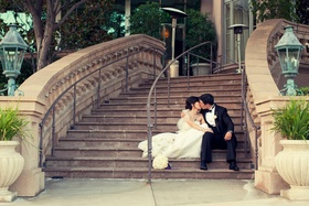 Bride and groom in wedding attire on steps