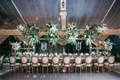 wedding reception head table wood chairs greenery flower chandelier tent string lights candelabra