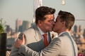 Gay men kissing on rooftop at wedding