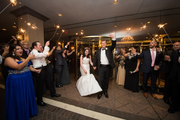 bride in martina liana groom in hugo boss run past sparklers for grand exit