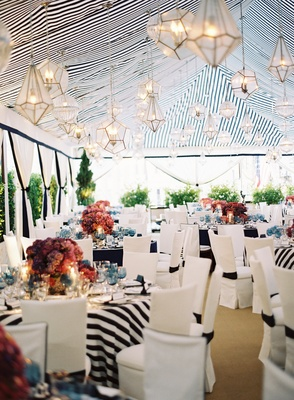Guest tables under blue and white striped tent