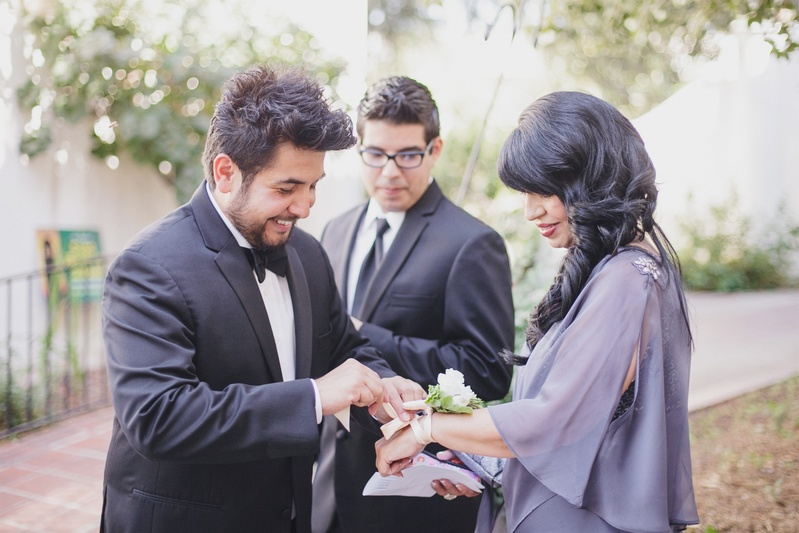 Groom puts corsage on mother in purple dress