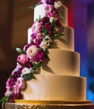 four tier wedding cake with smooth frosting and fresh pink flowers cascading down the side