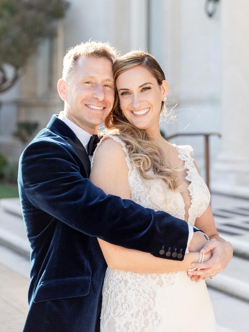 groom in navy velvet suit jacket hugging bride in pnina tornai from behind