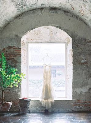 wedding dress hanging in window of old building in antigua guatemala liancarlo spanish lace