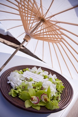 Plate of green orchids under parasol at beach wedding