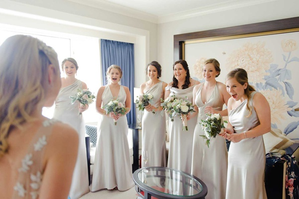bride in bridal suite showing bridesmaids her wedding dress for first time silver gowns bouquets