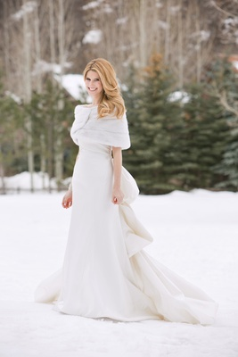 Bride wearing ivory wedding dress and fur shawl