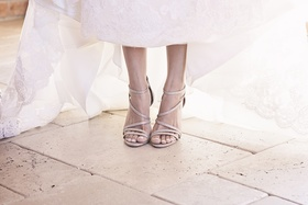 Bride wearing strappy sandal wedding heel shoes by Badgley Mischka and french manicure pedicure