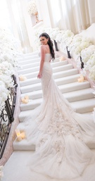 bride in inbal dror wedding dress with dramatic embellished train on stairs covered in flowers