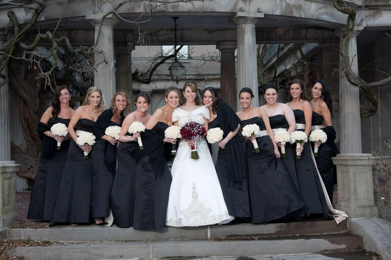 Bride with bridesmaids in strapless black gowns with white sashes and bouquets