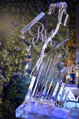 Wedding monogram on ice sculpture at reception bar