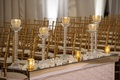 gold and crystal votive candles along aisle on mirror stand