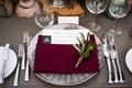 wedding reception grey wash wood table wood plank riser burgundy napkin sprig of greenery silver