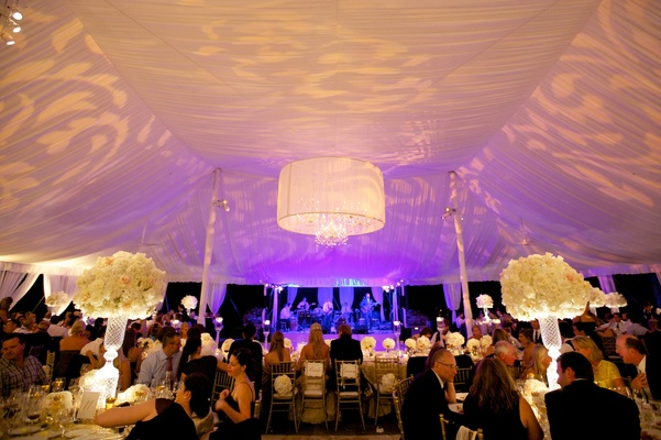 Tent wedding dinner service with violet lighting