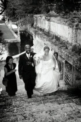 Black and white picture of father of bride walking bride up stairs