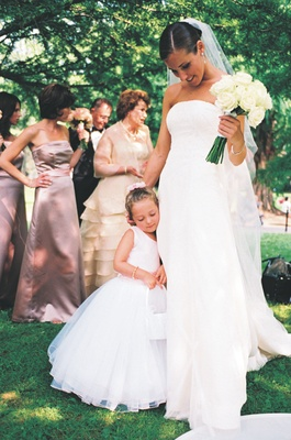 Flower girl dressed in white ball gown with light pink details