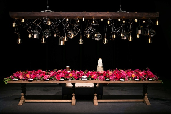 wooden table with long pink floral arrangement under unique geometric lighting concept bulbs