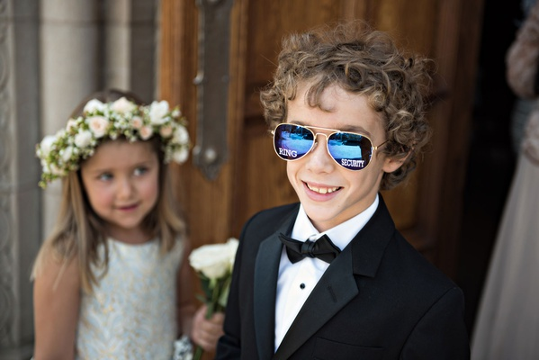Ring bearer in tuxedo and bow tie with mirror aviator sunglasses that say ring security on the lense