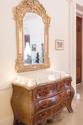 wedding reception at oheka castle antique chest dresser with escort cards candlelight gold mirror
