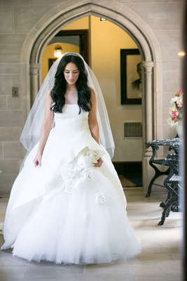 Bride in monique lhuillier wedding dress with peplum and white flower accents veil long brown hair