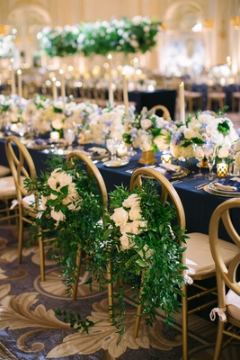 wedding reception head table navy blue linens gold chairs greenery and white flowers on bride groom