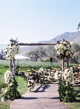 Rustic tree trunk arch over wood plank ceremony aisle