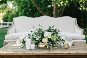Jillian Murray and Dean Geyer wedding reception lounge area settee with wood table green white