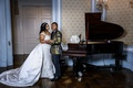 bride in stephen yearick and groom in gold and black jacket pose by grand piano