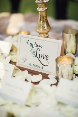 Escort card table with white rose petals, gold mercury glass vessel, Instagram wedding hashtag card