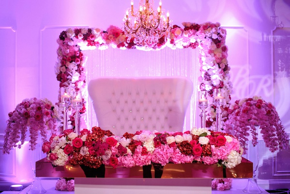 purple lighting sweetheart table white tufted settee pink red purple flowers orchids roses