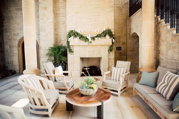 stone fireplace green garland with candles lounge area