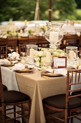 Tented wedding reception with table covered in tan tablecloth and white fabric, candles