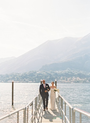 wedding portrait bride and groom arm in arm walking up dock lake como italy destination wedding