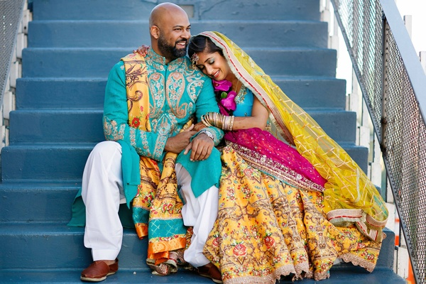 pakistani couple in traditional mehndi attire of yellow blue pink and white with beads and jewels