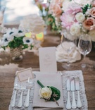 Rustic wood reception table with lace place mat tan napkin and white rose decoration