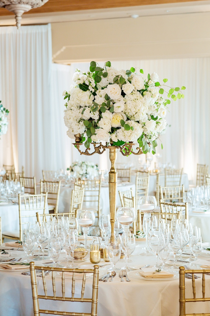 white roses and eucalyptus leaves on thin gold stand