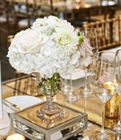rose, hydrangeas, and mum centerpiece in glass vase on a mirrored base